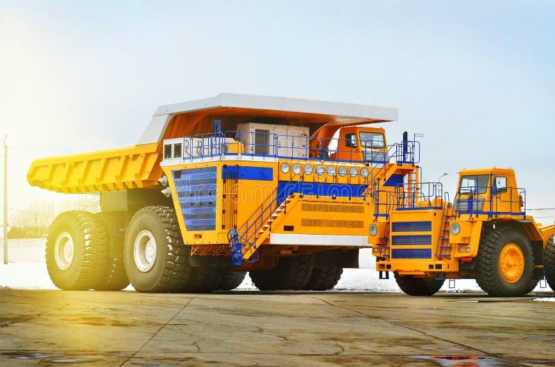 De vrachtwagen van de mijnbouwstortplaats bij zonsondergang op een concrete bestrating stock foto's