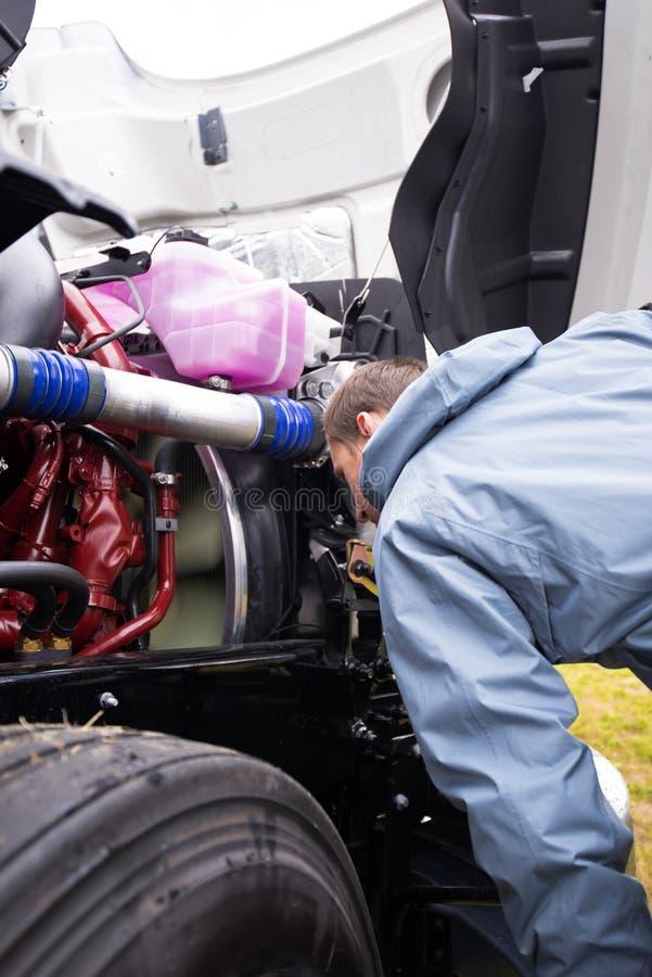 De vrachtwagenchauffeur inspecteert de lopende motor van grote semi vrachtwagen stock fotografie