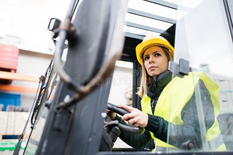 De vrachtwagenchauffeur van de vrouwenvorkheftruck op een industriezone stock fotografie