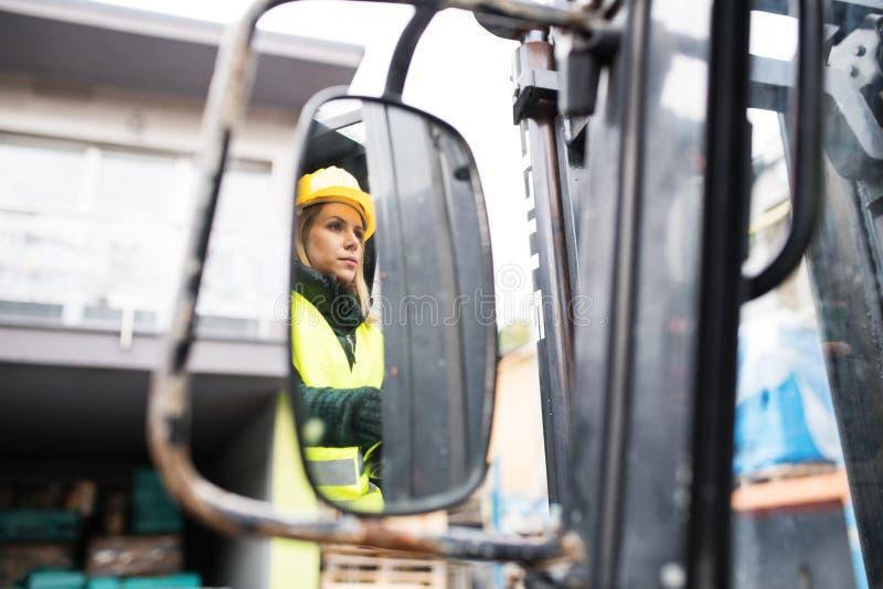 De vrachtwagenchauffeur van de vrouwenvorkheftruck op een industriezone royalty-vrije stock afbeelding