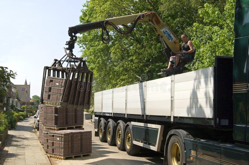 De vrachtwagenchauffeur, wegbouwer maakt vrachtwagenstraatstenen leeg royalty-vrije stock foto's