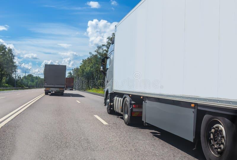 De vrachtwagens gaat op de weg stock afbeeldingen