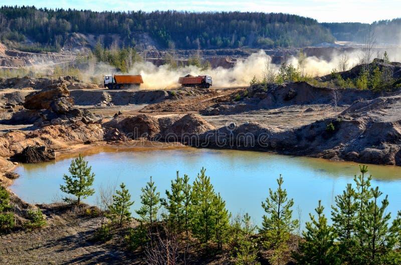 De vrachtwagentransporten van de mijnbouwstortplaats zand en andere mineralen in de steengroeve stock afbeeldingen