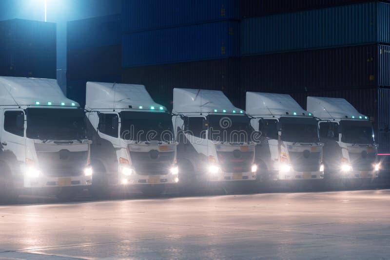 De vrachtwagenvloot parkeert bij containeryard bij nacht zoals voor vervoer en logistiekconcept royalty-vrije stock foto's