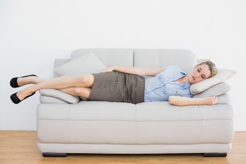 De vreedzame liggende slaap van de blonde elegante onderneemster op laag stock foto