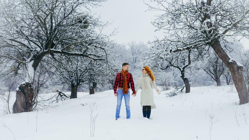 De vreedzame mooie die handen van de paarholding en het lopen langs de weg langs het de winterbos met pluizige sneeuw wordt behan stock afbeeldingen