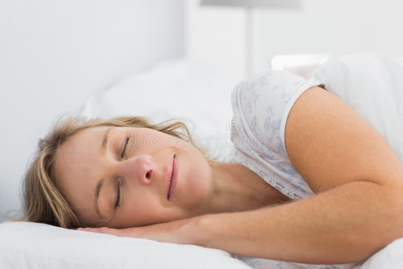 De vreedzame slaap van de blondevrouw in bed stock fotografie