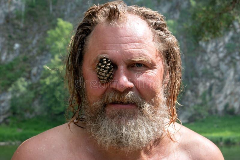 De vreemde grootvader kijkt als een gek of grappig karakter van het bos en de bergen Een bejaarde met een baard en een lang haar stock foto's