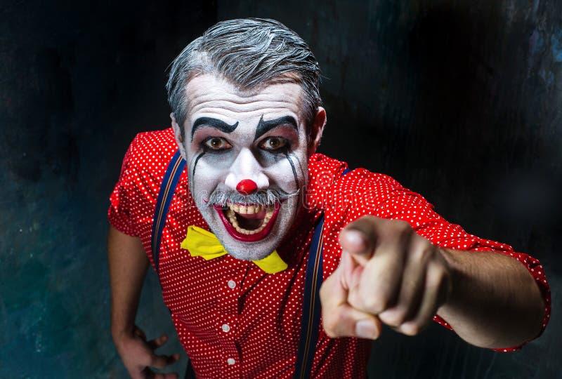De vreselijke clown en Halloween als thema hebben: Gekke rode clown in een overhemd met bretels royalty-vrije stock afbeeldingen