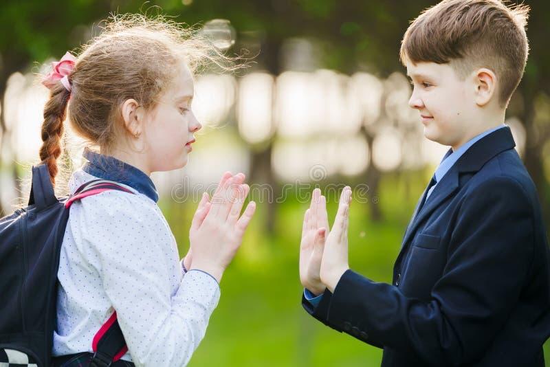 De vriend die van het schoolkind slaand handen geniet van stock foto