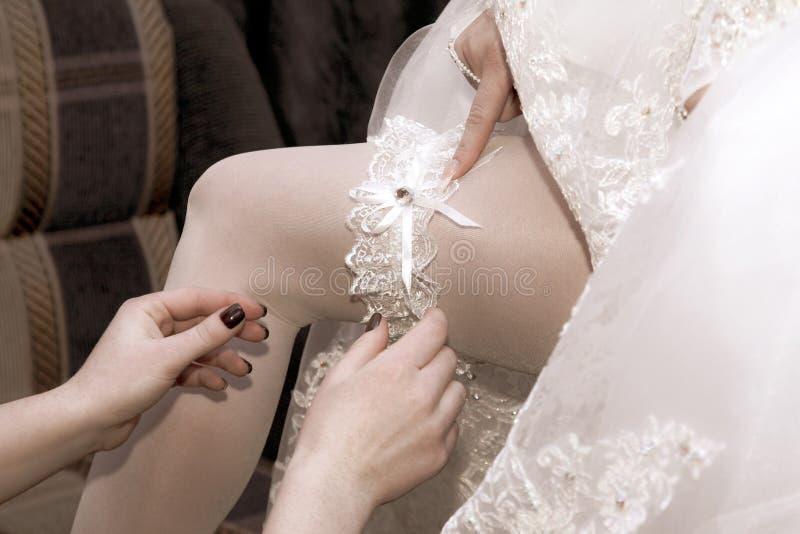 De vriend van de bruid draagt haar huwelijkskouseband royalty-vrije stock fotografie
