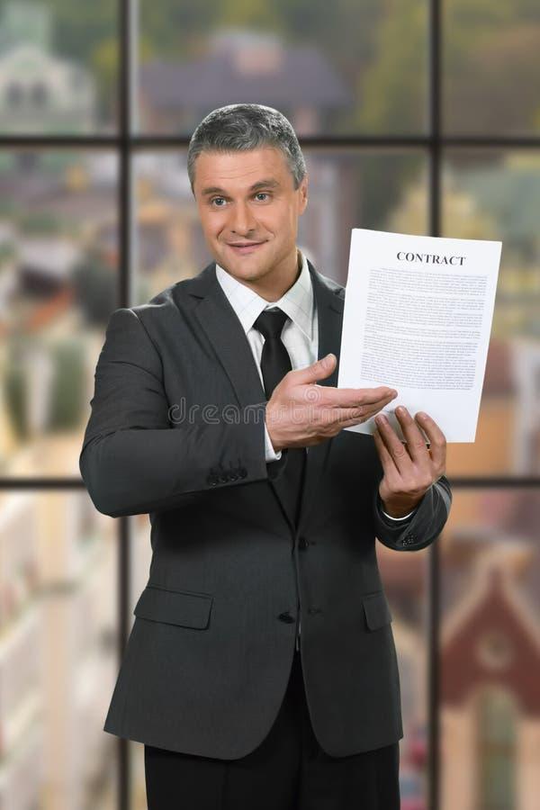 De vriendelijke zakenman toont arbeidsovereenkomst stock afbeelding