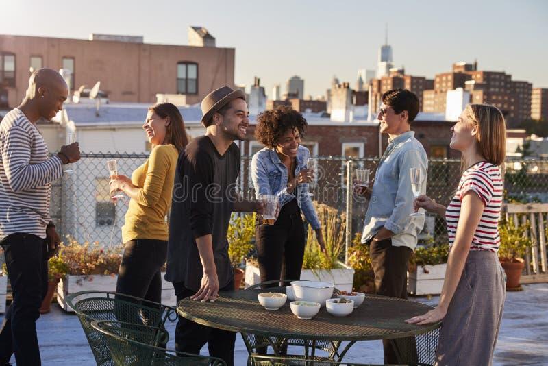 De vrienden bevinden zich sprekend bij een partij op een dak van New York stock afbeelding