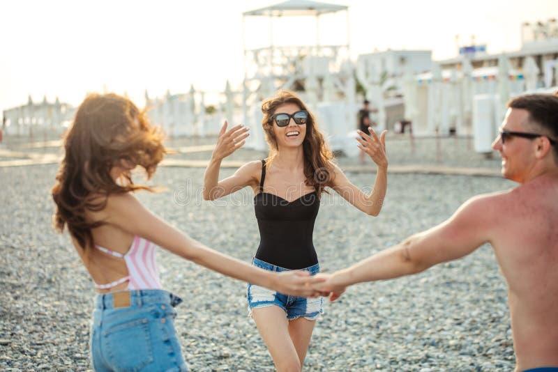 De vrienden dansen op strand onder zonsondergangzonlicht, die gelukkige pret hebben, genieten van royalty-vrije stock afbeelding