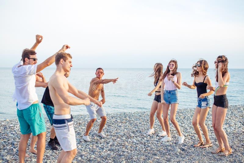 De vrienden dansen op strand onder zonsondergangzonlicht, die gelukkige pret hebben, genieten van royalty-vrije stock foto's