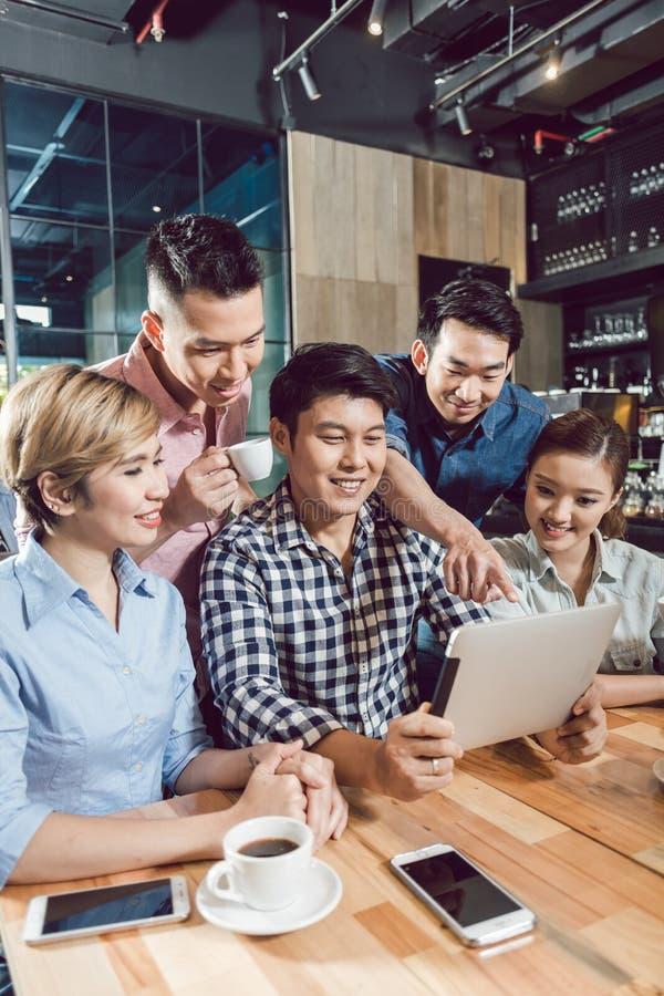 De vrienden die digitale tablet in de koffie bekijken winkelen stock fotografie
