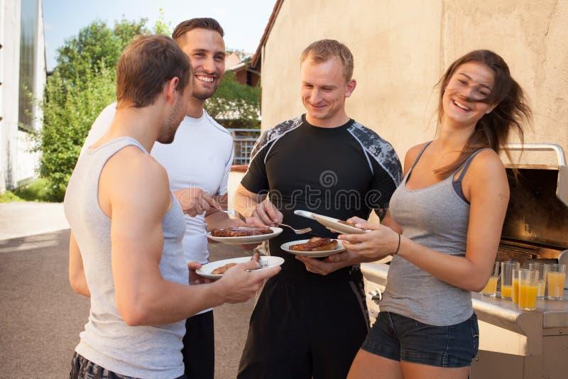 De vrienden die een barbecue na geschiktheid hebben werken uit stock afbeelding