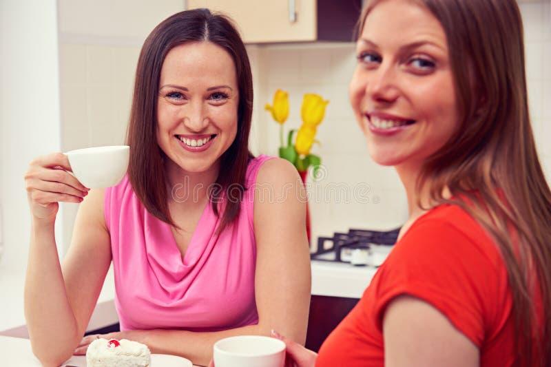 Vrienden die koffie drinken en camera bekijken royalty-vrije stock foto