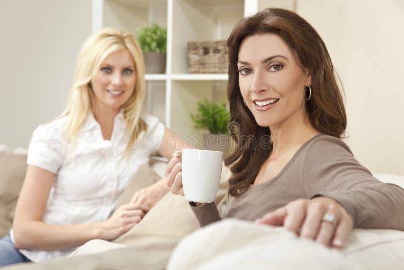 De Vrienden die van vrouwen Thee of Koffie thuis drinken royalty-vrije stock foto's