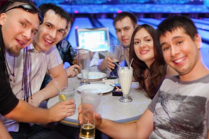 De vrienden drinken bier en cocktails in kegelen royalty-vrije stock afbeelding