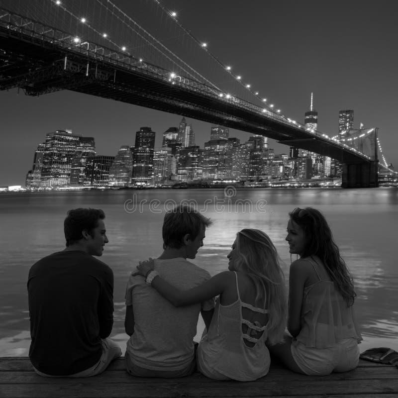 De vrienden groeperen achtermening bij zonsondergangpret New York stock afbeeldingen