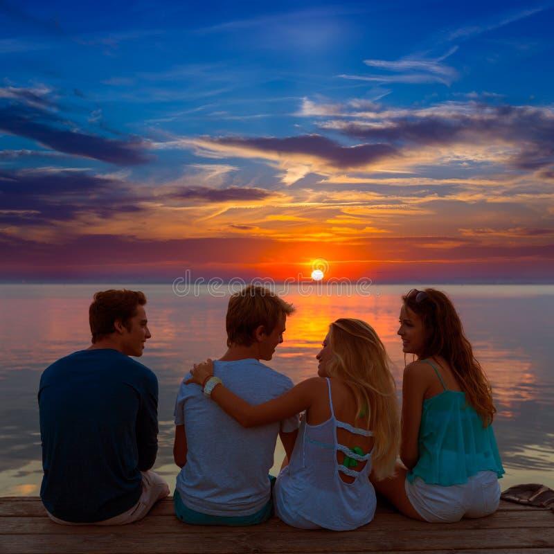De vrienden groeperen achtermening samen bij zonsondergangpret stock afbeelding