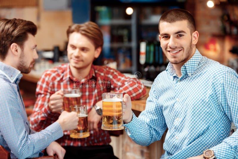 De vrienden hebben een bier bij de bar stock afbeeldingen