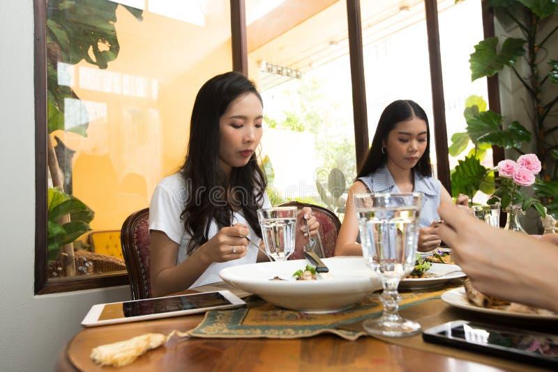 De vrienden hebben lunch samen op houten lijst eten stock foto
