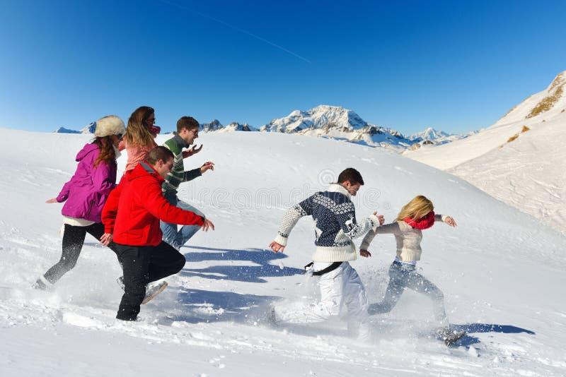 De vrienden hebben pret bij de winter op verse sneeuw stock foto's