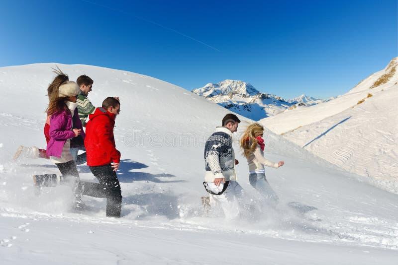 De vrienden hebben pret bij de winter op verse sneeuw stock afbeeldingen