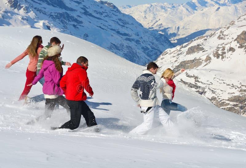 De vrienden hebben pret bij de winter op verse sneeuw stock foto
