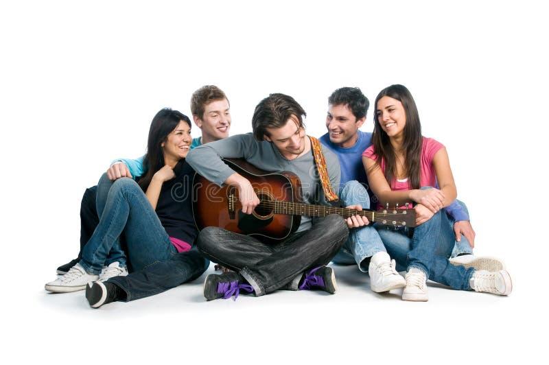 De vrienden hebben samen pret en het spelen gitaar stock foto