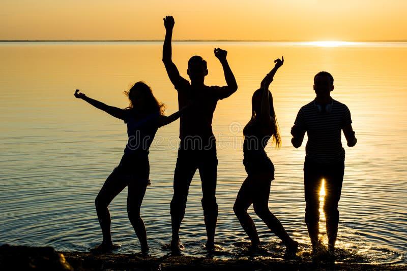 De vrienden, de kerels en de meisjes, studenten dansen bij zonsondergangbackgrou stock foto's