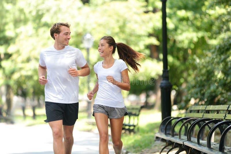 De vrienden koppelen het gelukkige lopen samen in stadspark stock afbeelding