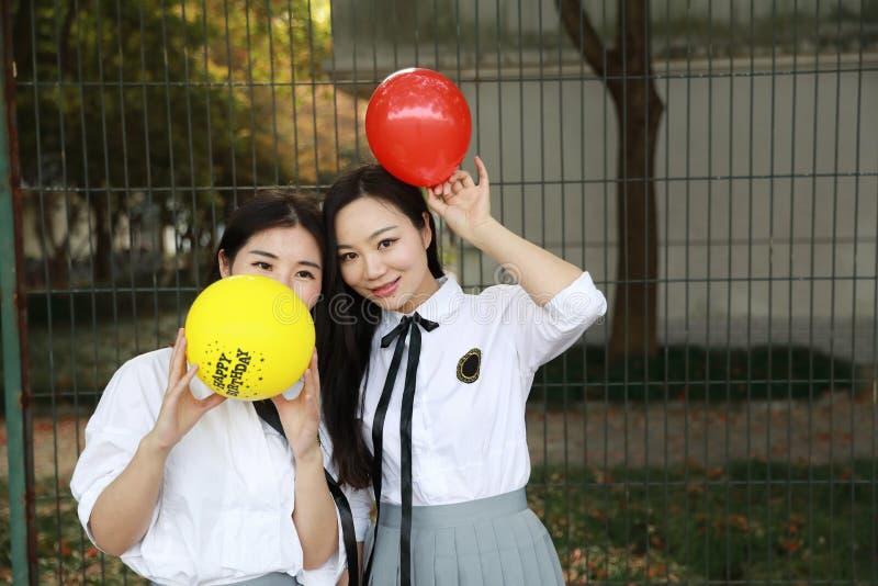 De vrienden leuke aanbiddelijke mooie studenten van het Bestie blazen de goede beste meisje ballon op speelplaatsschool royalty-vrije stock foto
