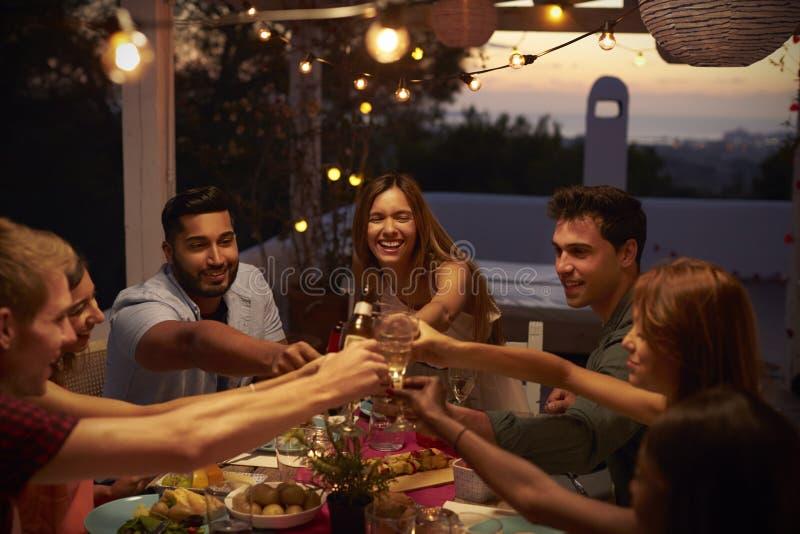 De vrienden maken een toost bij een dinerpartij op een terras, omhoog sluiten royalty-vrije stock foto's