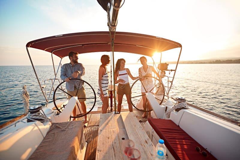 De vrienden op vakantie reizen samen op boot en genieten van bij de zomerdag stock fotografie