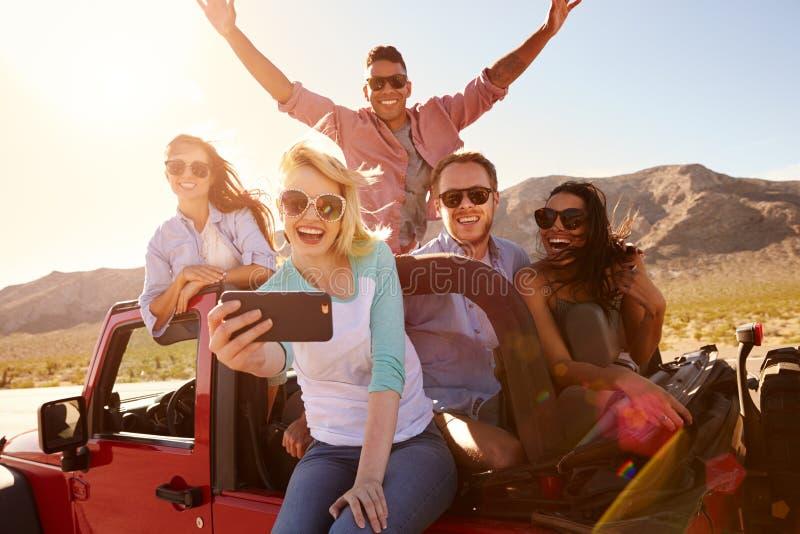 De vrienden op Weg halen in Convertibele Auto over die Selfie nemen royalty-vrije stock foto's