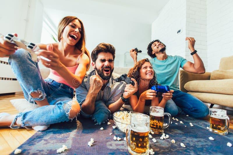 De vrienden spelen videospelletjes die samen thuis, pret hebben stock foto