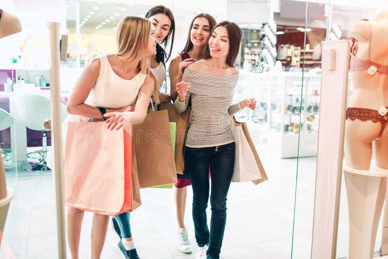 De vrienden spreken onder zich en lopen in lingerieopslag Zij houden zak De meisjes winkelen en stock foto's