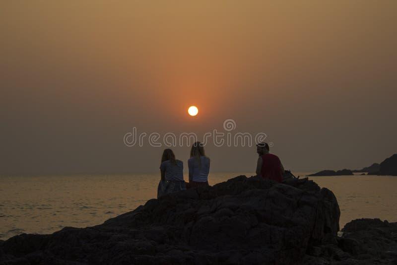 De vrienden, twee meisjes en een kerel zitten op een rots tegen de achtergrond van oceaan en purpere roze grijs royalty-vrije stock afbeelding