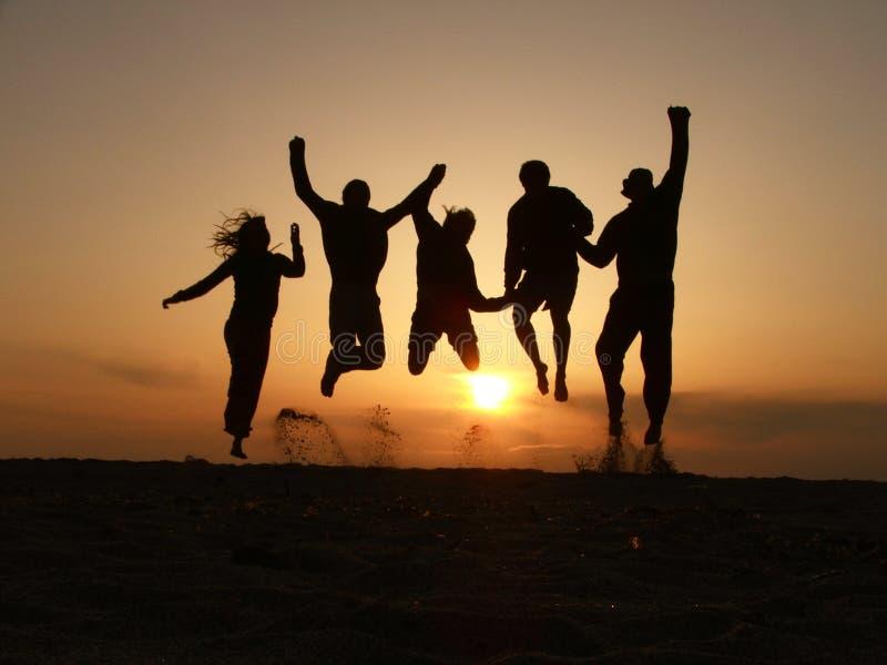 De vrienden van de zonsondergang het springen stock afbeeldingen
