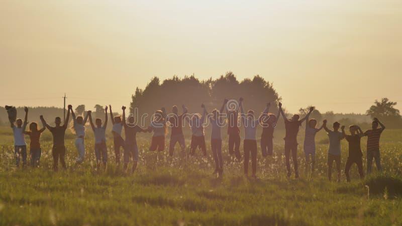 De vrienden van schoolkinderen stuiteren bij zonsondergang in de zon stock afbeeldingen