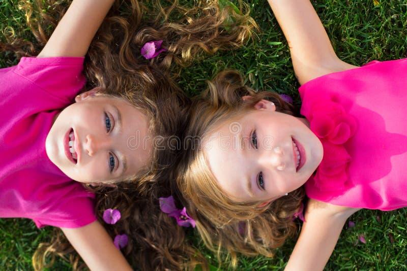 De vriendenmeisjes die van kinderen bij tuingras het glimlachen liggen royalty-vrije stock afbeeldingen