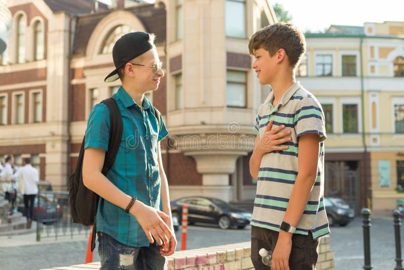 De vriendschap en de mededeling van twee tieners zijn 13, 14 jaar oud, de achtergrond van de stadsstraat royalty-vrije stock foto