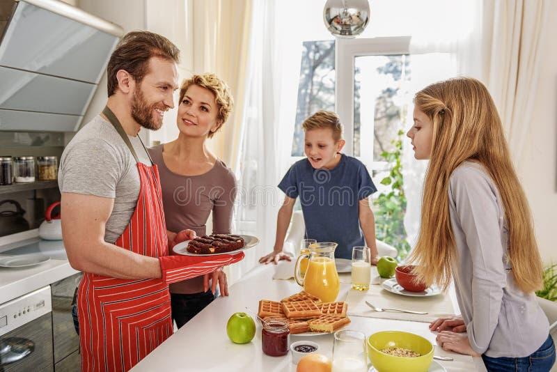 De vriendschappelijke familie is bereid om ontbijt te hebben royalty-vrije stock foto's