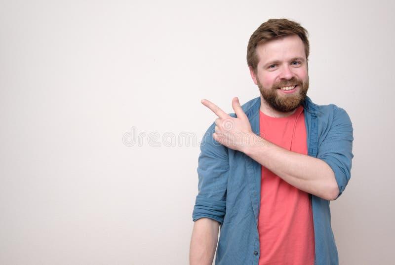 De vriendschappelijke, glimlachende mannelijke mens toont zijn vinger op een witte muur, met exemplaarruimte en onderzoekt de cam stock foto's