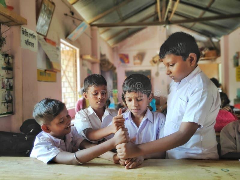 de vriendschappelijke jonge geitjes in school eenvormige speelspelen met smily ziet in een lokale dorpslage school onder ogen stock fotografie