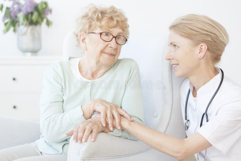 De vriendschappelijke oude dame van het verpleegstersbezoek stock fotografie