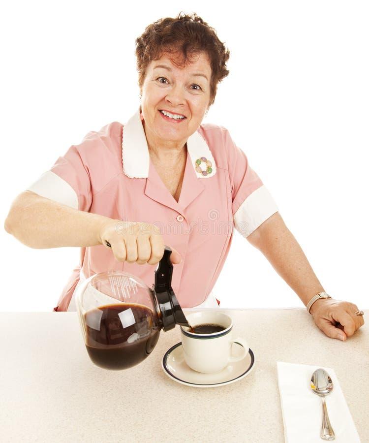 De vriendschappelijke Serveerster giet Koffie royalty-vrije stock afbeeldingen